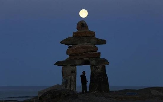 A man looks at a giant inukshuk as the moon rises above it in Rankin Inlet, Nunavut in this file photo from August 21, 2013.